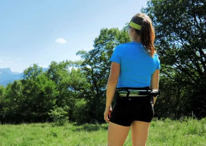 Anaïs Chevalier portant la running belt Sammie Trail avec des bâtons accrochés dans le dos