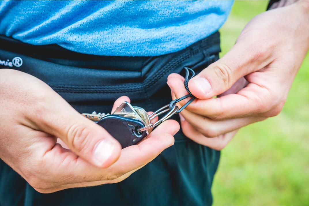 Un runner ouvre de la ceinture de Running Sammie® Mini pour récupérer un objet