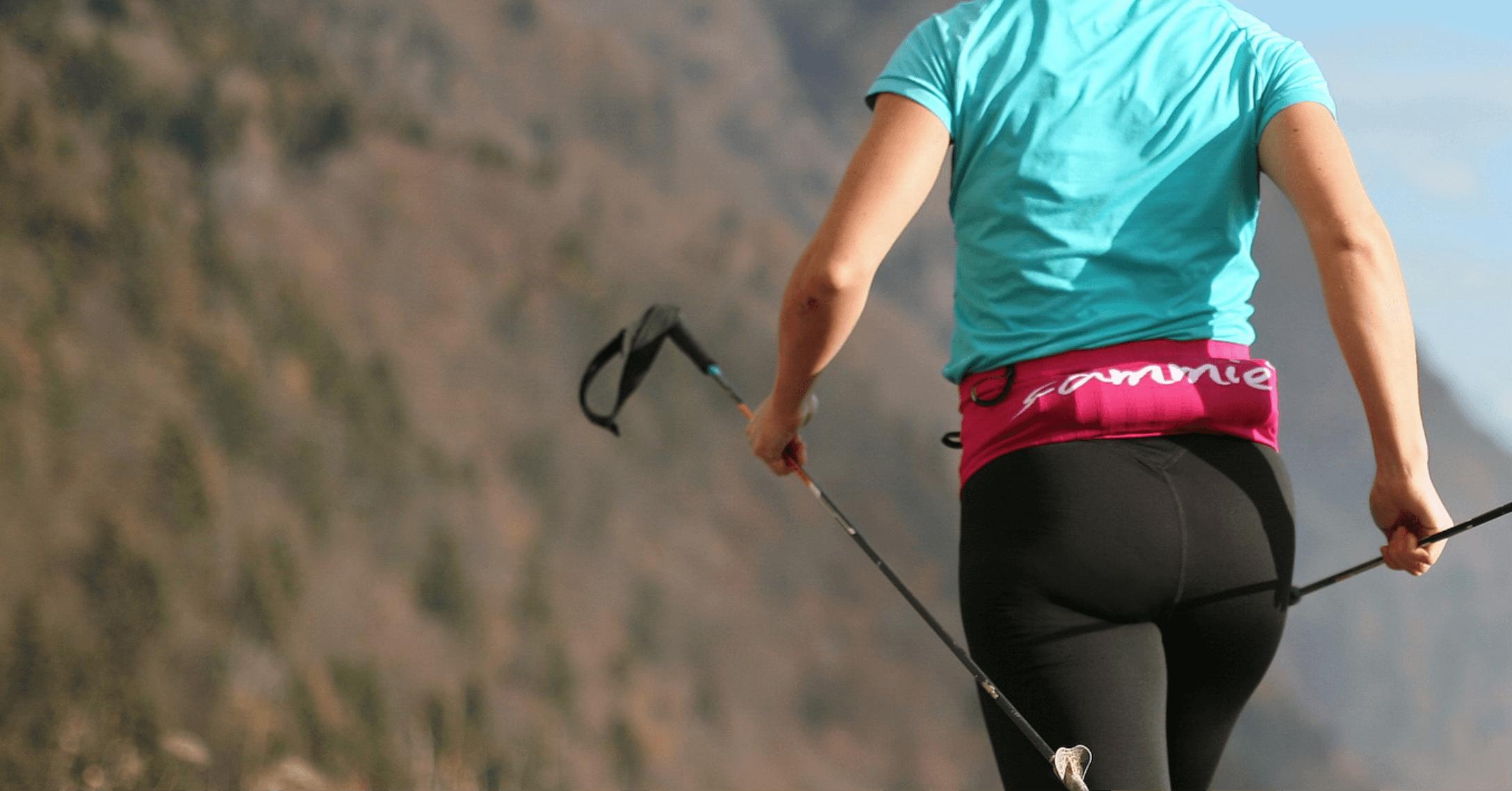 Une sportive portant la Sammie® V2 remplie avec une gourde souple pendant une run le long d'une crête en montagne