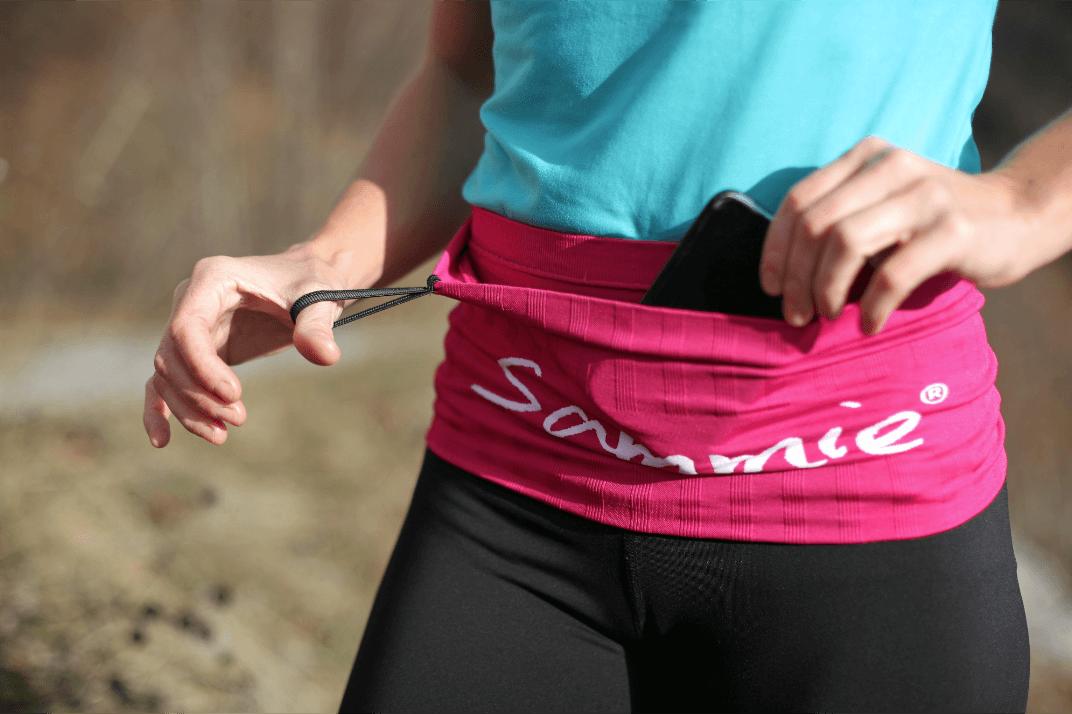La running belt dans sa version rose portée par une sportive qui récupère à l'intérieur de la ceinture son téléphone portable